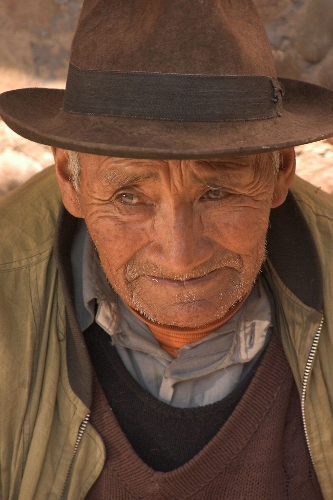An old man waits at a market in Peru