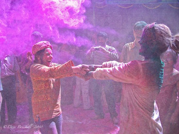 dancing in a powder of colours during holi festival in India