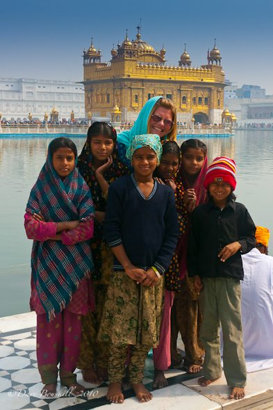 tourist poses with children at Golden Temple