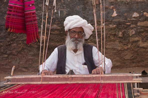 An Old mand at work in India weaving a carpet