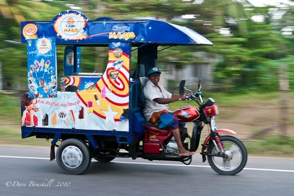 an ice cream man drives his three wheeler