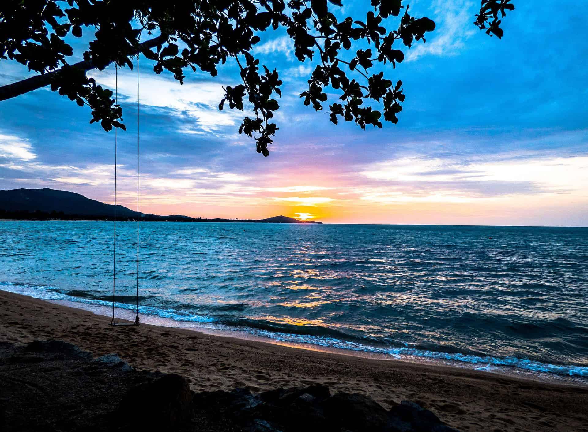 swing on thailand beach at sunset