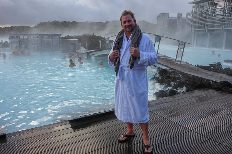 standing in robe at pool of blue lagoon in iceland