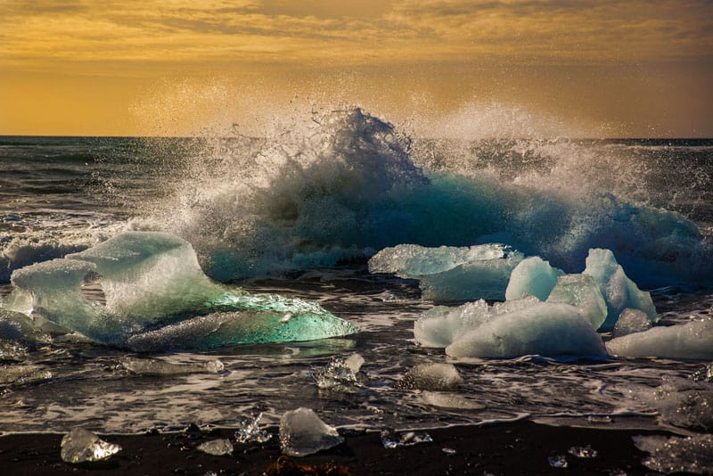 waves crashing on an iceberg in iceland