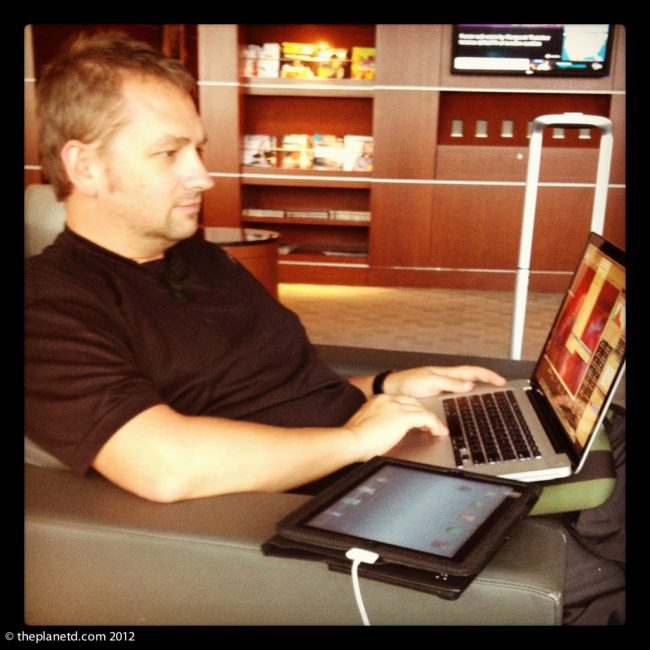 working in an airport lounge ipad and computer