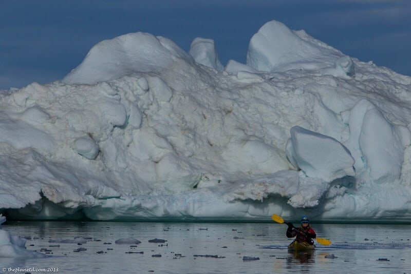 kayaking in Greenland Deb near large iceberg