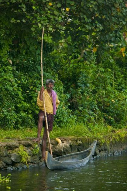 man with bamboo pole on riverbank in  backwatres