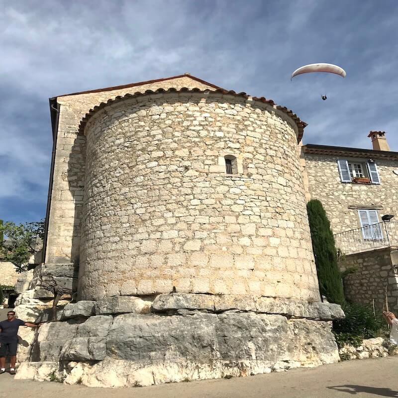 paraglider over medieval town french riviera