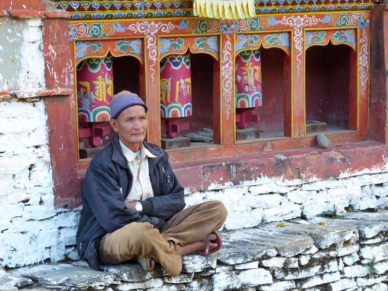 man by prayer wheels in east india
