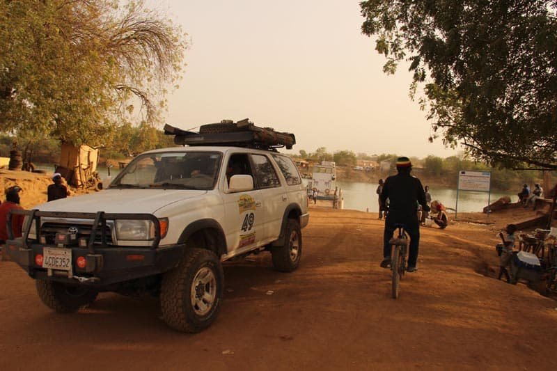 bamako rally cyclist beside overland truck