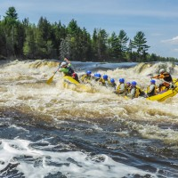 Large whitewater raft buckling in the rapids