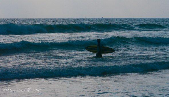 surfer walks through waves in sri lanka