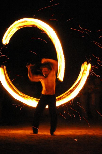 Poi performer spins fire