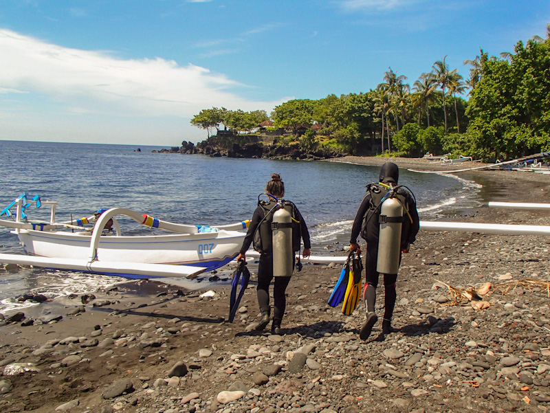 scuba divers walking on beach in Bali to Tulamben shipwreck