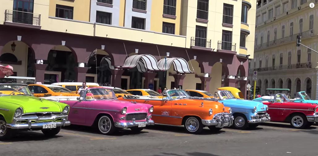 cars lined up along central park havana