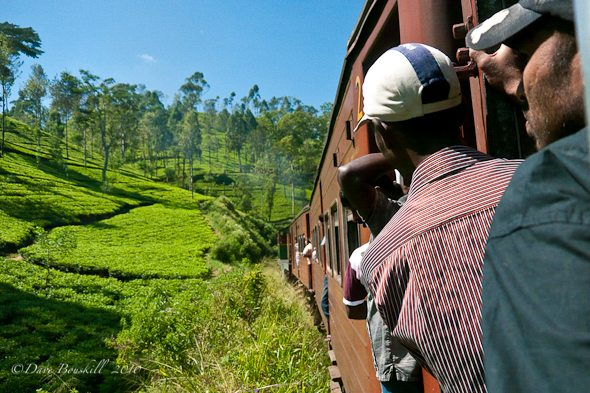 men hang out of trains in Sri Lanka