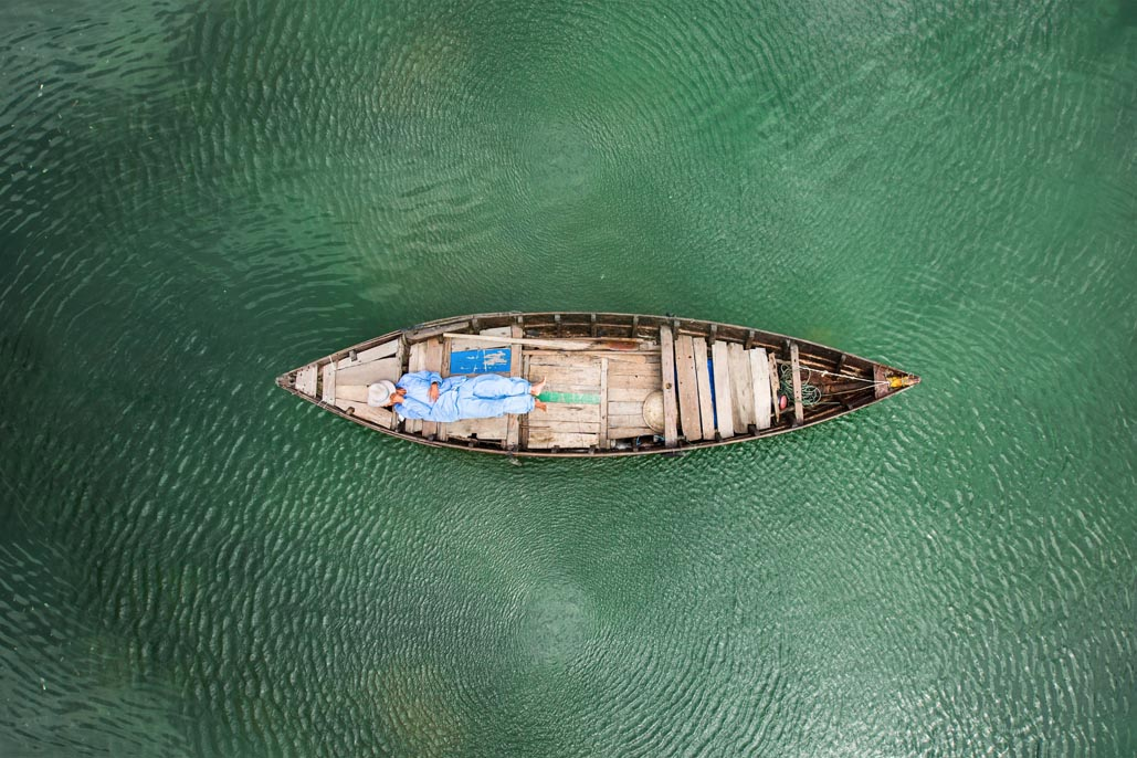 fisherman sleeping in boat in vietnam waters