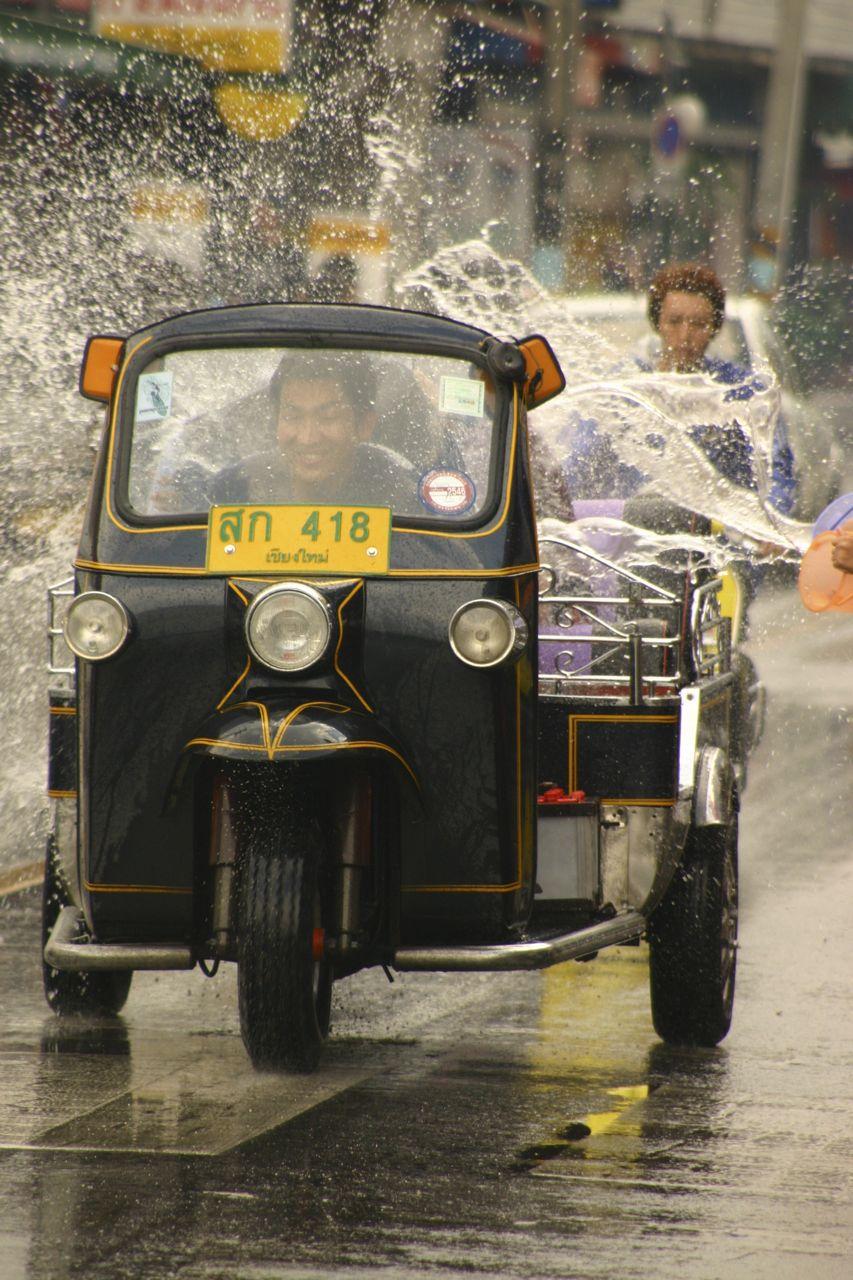 Tuk tuk Drives through water being thrown at Songkran Festival in Thailand