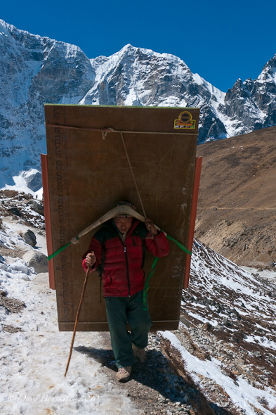 sherpa carrying plywood to everest base camp