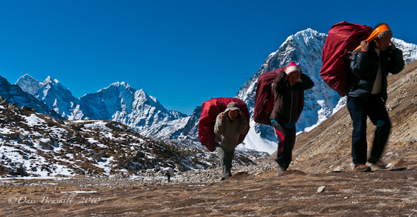 sherpas carry heavy loads to everest base camp