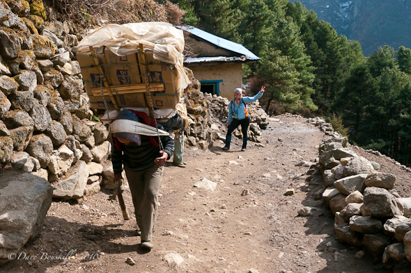 Sherpa carries heavy load up to Everest Base Cmp